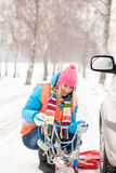 Woman with tire chains car snow breakdown. Smiling fixing winter Royalty Free Stock Images