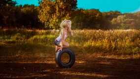 Woman on tire in countryside Royalty Free Stock Photography