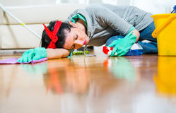 Woman tired of cleaning sleeping on the floor Stock Images