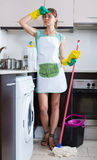 Woman tired during cleanup at kitchen Royalty Free Stock Images