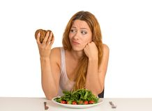 Woman tired of diet restrictions craving cookie. Young woman tired of diet restrictions deciding whether to eat healthy food or sweet cookies she is craving Royalty Free Stock Images