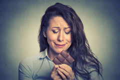 Woman tired of diet restrictions craving sweets chocolate. Portrait sad young woman tired of diet restrictions craving sweets chocolate  on gray wall background Stock Images