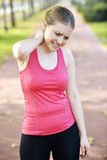 Woman tired and neckache. Running sport backache. Woman runner in pain while training for marathon in country road. Caucasian female athlete stock image