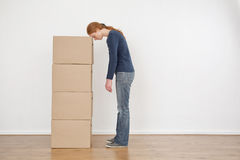 Woman Tired from Packing Boxes. A tired or exhausted young woman resting her head on a stack of carton moving boxes in an empty room Royalty Free Stock Image
