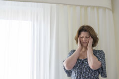 Woman tired to hang curtains and experiencing headache. Woman tired to hang curtains and experiencing a headache Royalty Free Stock Image