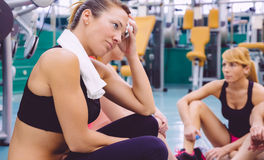 Woman tired with towel resting in the gym after Stock Images