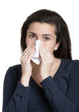 Woman with tissue. Pretty young woman with a cold blowing nose Stock Image