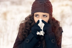 Woman with Tissue Outside Feeling Bad Cold Winter. Suffering ill girl with flue being cold holding paper napkin in wintertime Royalty Free Stock Images