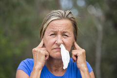 Woman with tissue in running nose and finger in ears Stock Image