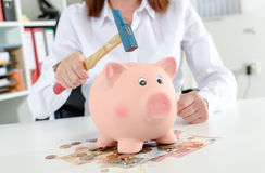 Woman about to break the piggy bank Royalty Free Stock Image