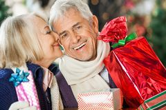 Woman About To Kiss Man Holding Christmas Presents Stock Images