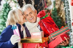 Woman About To Kiss Man Holding Presents Stock Image