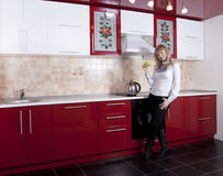 Woman to kitchen. Young woman to kitchen in red-white color Royalty Free Stock Photo