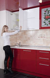 Woman to kitchen. Young woman to kitchen in red-white color Royalty Free Stock Image
