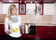Woman to kitchen. Young woman to kitchen in red-white color Stock Photography