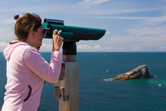 Woman to look through binoculars, island Stock Photos