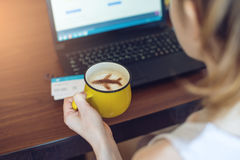 Woman to reserve or buy tickets online at laptop. Woman holds in her hands a Cup of coffee with the plane of the cinnamon working at a laptop and to reserve or Royalty Free Stock Photo