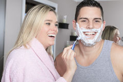 Woman to shave is boyfriend in bathroom Royalty Free Stock Photography