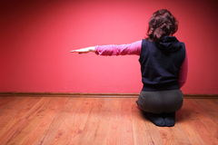 Woman to sit on the floor. Woman to sit on floor on red wall background Royalty Free Stock Images
