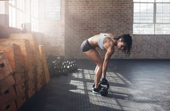 Woman about to start her fitness regime. Full length shot of fitness woman doing crossfit exercising with kettle bell. Determined female model about to start her Royalty Free Stock Image