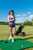 Woman about to strike golf ball Stock Photography