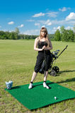 Woman about to strike golf ball Stock Images