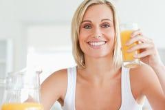 Woman toasting with orange juice Stock Photos