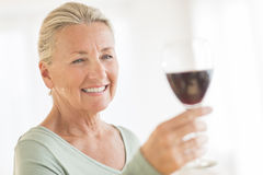 Woman Toasting Red Wineglass At Home. Happy senior woman looking away while toasting red wineglass at home Royalty Free Stock Image