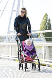 Woman with toddle. R sitting in pram on walk Royalty Free Stock Images