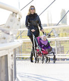 Woman with toddler. Sitting in pram on walk Stock Photo
