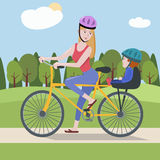 Woman and toddler on a bike at the park Stock Photo