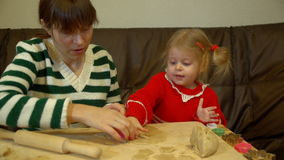 Woman and toddler girl preparing gingerbread for family Christmas eve dinner. stock video