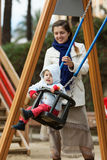 Woman with  toddler on swings Stock Image