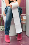 Woman in a toilet. With a big hank of sanitary paper Stock Photography