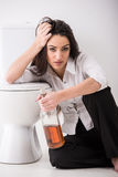 Woman in toilet. Drunk woman is sitting on the toilet floor and is holding a whisky bottle Stock Photos