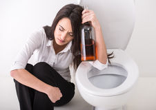 Woman in toilet. Drunk woman is sitting on the toilet floor and is holding a whisky bottle Stock Photography