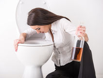 Woman in toilet. Drunk woman vomiting on a toilet bowl and is holding a bottle with alcohol Stock Photos