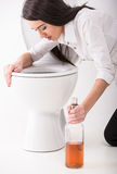 Woman in toilet. Drunk woman vomiting on a toilet bowl and is holding a bottle with alcohol Royalty Free Stock Photography