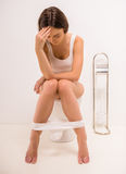 Woman in toilet. Using toilet. A young woman uses a toilet with a roll of toilet paper in his hand Royalty Free Stock Photos