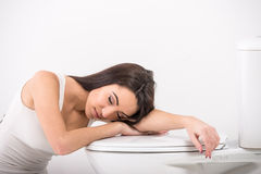 Woman in toilet. Young woman asleep in the toilet. White background Royalty Free Stock Photos