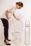 Woman in toilet. Young pregnant woman use the toilet, isolated on a white background Royalty Free Stock Images