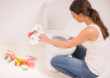 Woman in toilet. Young woman vomiting into the toilet bowl in the early stages of pregnancy or after a night of partying and drinking Royalty Free Stock Image