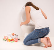 Woman in toilet. Young woman vomiting into the toilet bowl in the early stages of pregnancy or after a night of partying and drinking Royalty Free Stock Photos