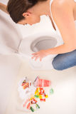 Woman in toilet. Young woman vomiting into the toilet bowl in the early stages of pregnancy or after a night of partying and drinking Stock Images