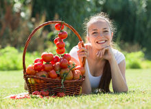Woman with tomato harvest in garden Stock Image