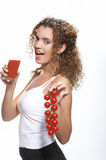 Woman with tomato juice. Half body portrait of young woman holding glass of tomato juice and tomatoes on vine, isolated on white background Stock Photography