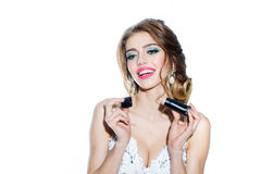 Woman with tone foundation. Young woman with pretty smiling face in elegant dress with red lips holding makeup tube with tone foundation in studio isolated on Royalty Free Stock Image