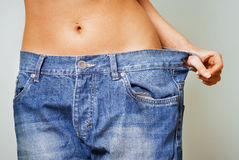 Woman with too large jeans after a diet. Close-up of a woman belly in a too big pants against grey background royalty free stock images