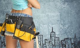 Woman in tool belt against stone wall with sketch Royalty Free Stock Image