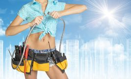Woman in tool belt, connects two flexible hose Stock Images